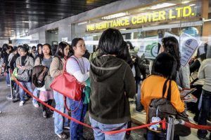 Filipino domestic helpers line up to send money at a remittance center in the central district of Hong kong on November 30, 2008, Remittances sent home by overseas Filipino workers grew 16.9 percent year on year in September despite earlier fears the global financial crisis could see a decline, the central bank said. They sent back 1.3 billion USD during the month, while the total for the first nine months of the year reached 12.3 billion USD, up 17.1 percent from a year ago, the central bank said. AFP PHOTO/TED ALJIBE (Photo credit should read TED ALJIBE/AFP/Getty Images)