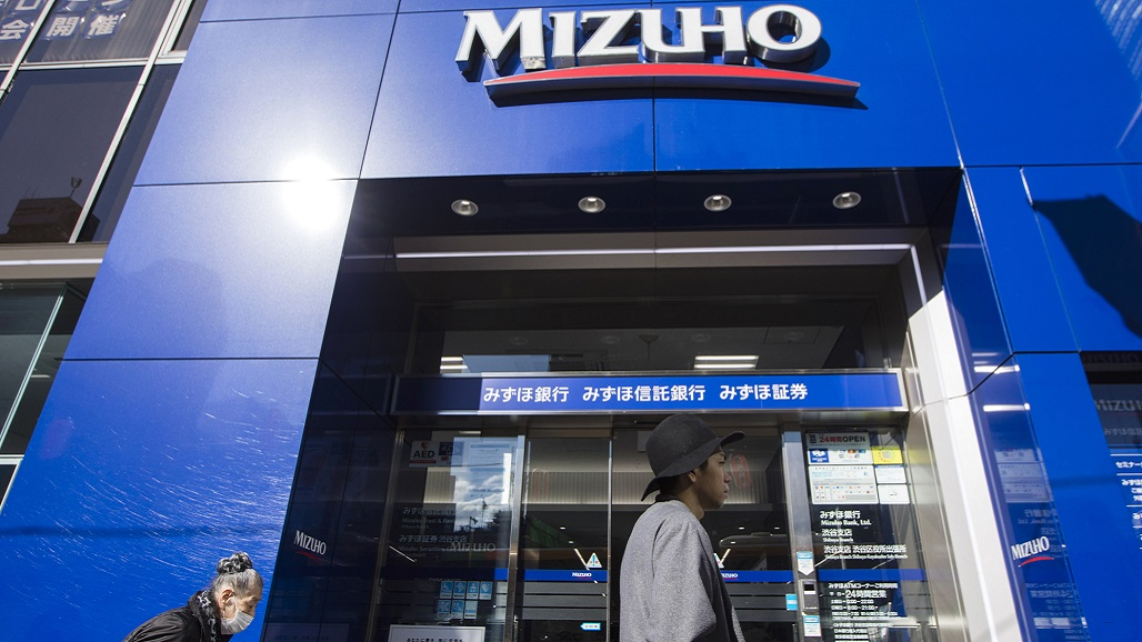 Passersby walk past a Mizuho Bank Ltd. branch in the Shibuya district of Tokyo, Japan, on Thursday, Nov. 16, 2017. Japan's economy grew for a seventh straight quarter, its longest expansion since 2001, as a recovery in exports and rising business investment offset a decline in consumer spending. Photographer: Keith Bedford/Bloomberg
