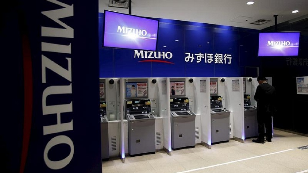 A man stands in front of an ATM of Mizuho Financial Group's Mizuho bank at its branch in Tokyo, Japan, May 15, 2015. Mizuho Financial Group Inc reported on Friday a smaller than forecast 11 percent fall in annual profit, helped by a strong stock market and its overseas expansion. REUTERS/Yuya Shino - RTX1D1Y3