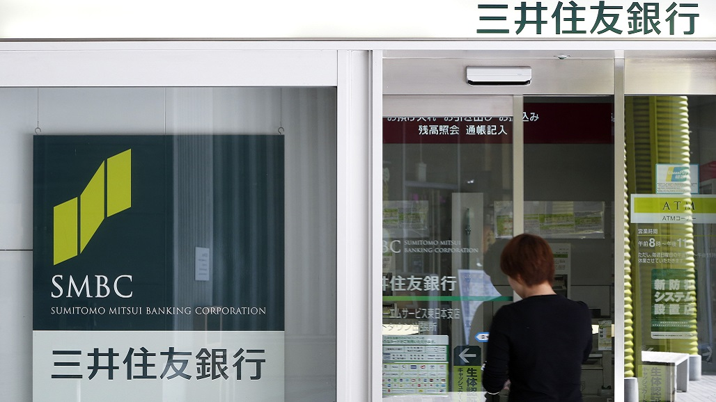 A woman enters a Sumitomo Mitsui Banking Corp. branch in Tokyo, Japan, on Tuesday, Nov. 5, 2013. Sumitomo Mitsui Financial Group Inc., Japan's second-biggest bank by market value, raised its annual profit forecast 29 percent after gains in fee income and the value of its stock holdings boosted first-half earnings. Photographer: Kiyoshi Ota/Bloomberg