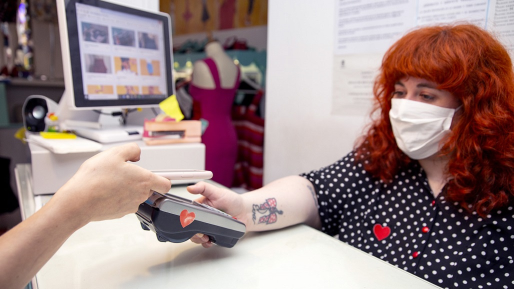 MADRID, SPAIN - JUNE 02: Fashion designer Eva Arinero at the register of her boutique Lady Cacahuete helping a customer with contactless payment via smartphone on June 02, 2020 in Madrid, Spain. Lady Cacahuete is a brand inspired by the 50s' fashion whose clothes are designed, patterned and made in Spain. Although they have been able to continue selling via their online store, due to the preventive measures taken in Spain during the Coronavirus (COVID-19) crisis they have had to close their physical store located in the center of Madrid for almost four months. Their revenue in that period has fallen over 65% compared to the previous year. The shop has been open to the public with all the appropriate sanitary measures since the end of May. Lady Cacahuete participated in the EGO Mercedes Benz Madrid Fashion Week 2013 and 2014 editions. (Photo by Patricia J. Garcinuno/Getty Images)